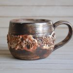 Hand made ceramic mug with clay bumps around the center, brown clay with slip and white glaze interior