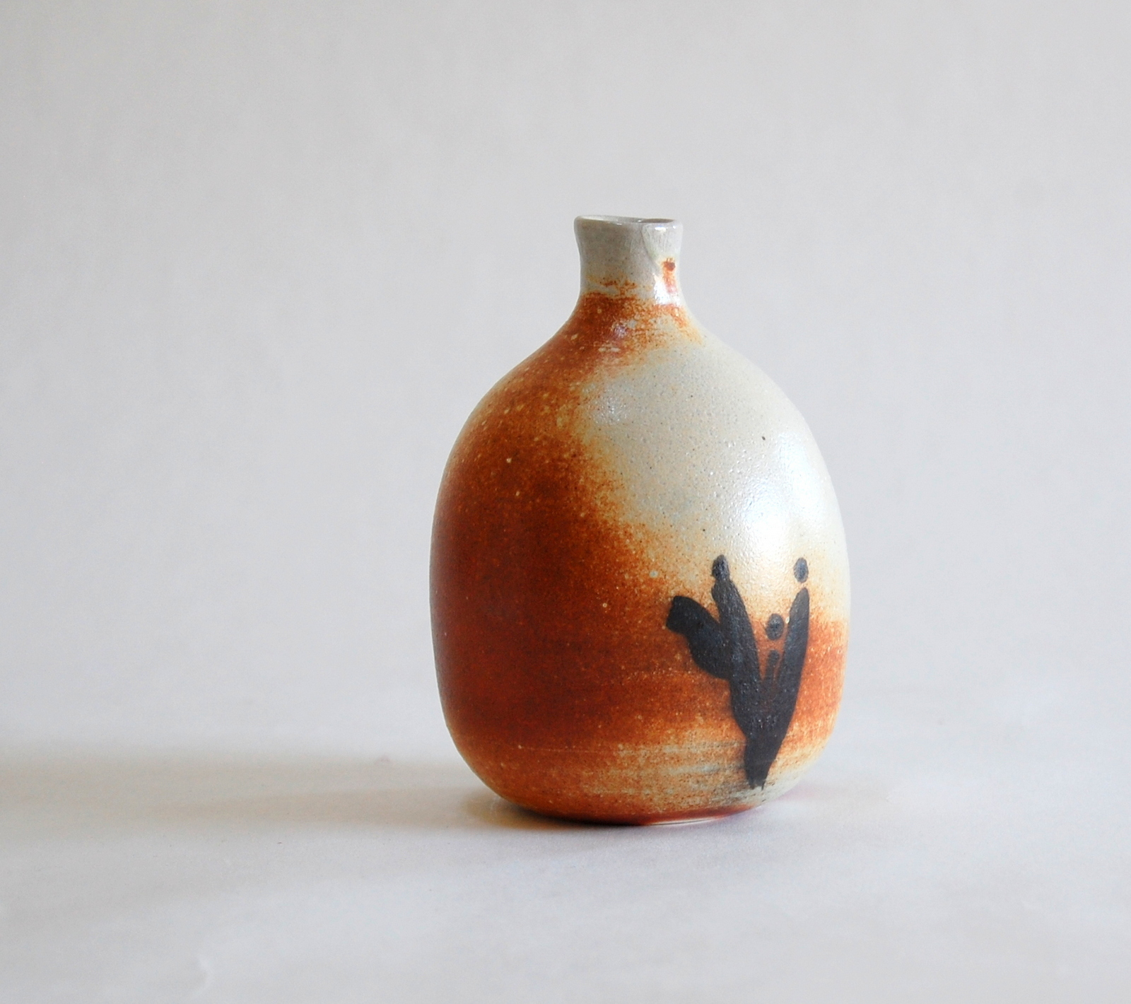 Small 4 inch high soda fired bottle, white clay with black hand-painted plant design
