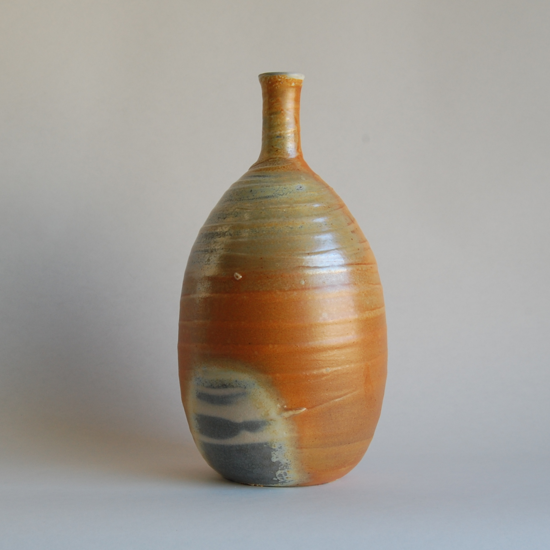 Orange and irridescent gray soda fired hand made ceramic bottle