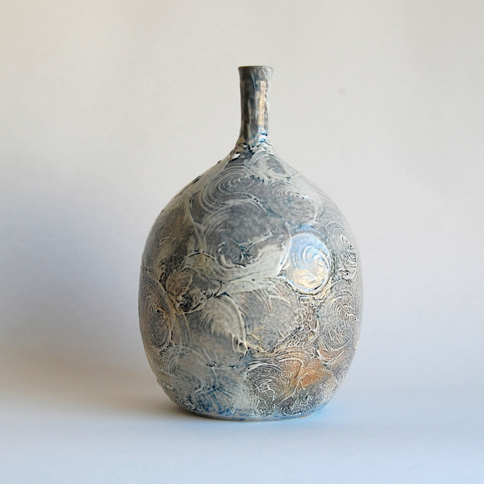 Blue and white hand made soda fired bottle with swirly slip surface and orange flashing