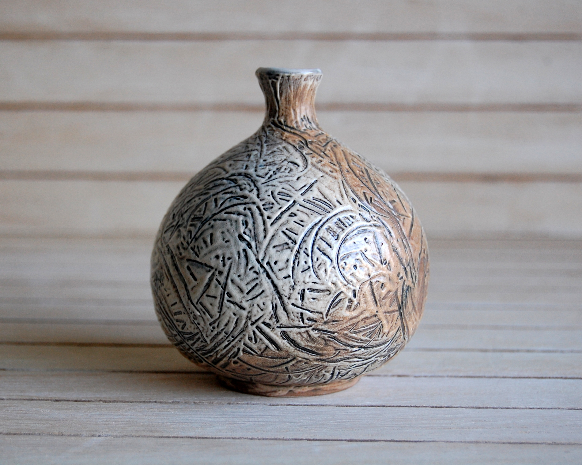 Little soda fired bottle, 4.5 inches high, with stained slip design and light brown flashing