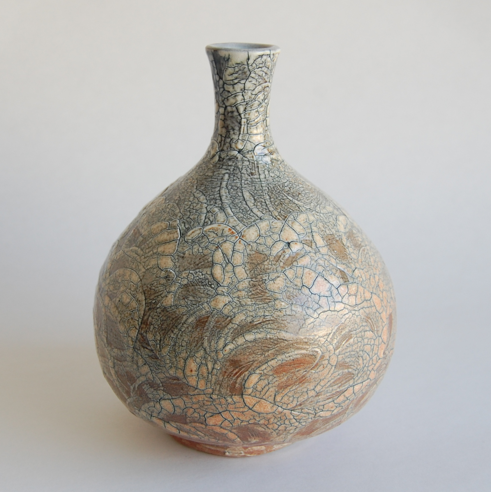 Wheel thrown ceramic bottle with swirled and crackled slip design, soda fired