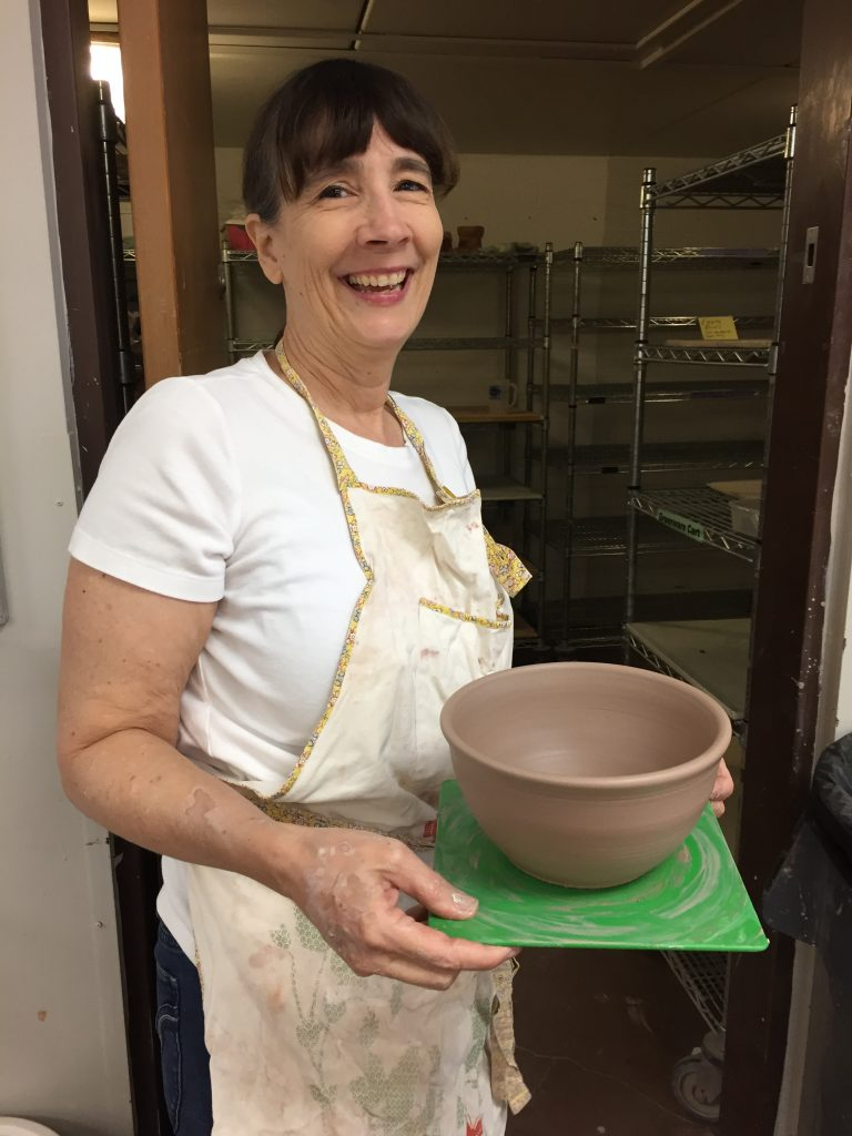 Ceramic artist Gabrielle holding a bowl she just made out of clay